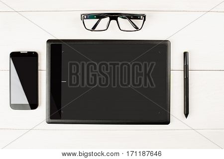Graphic Tablet With Eyeglasses And Smartphone On A White Wooden Table