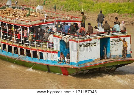 CHHOTA DHULANDI, BANGLADESH - FEBRUARY 19, 2014: Unidentified people cross Padma river on Daulatdia ferry boat at Chhota Dhulandi, Bangladesh. Passenger ferry boats are often overloaded in Bangladesh.