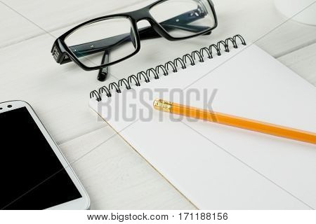 Pencil With Open Notepad, Glasses And Smartphone Close-up Shot