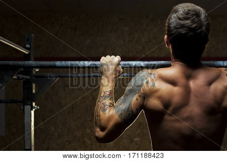 Back view of muscular man with naked torso doing pull ups exercise on horizontal bar. Fitness, gymnastics workout in gym.