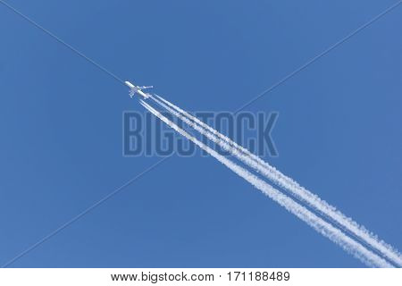 jet with four engines left contrail in the clear sky