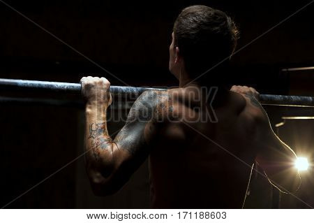 Back view of male muscular adult pulling up. fitness, gymnastics workout in gym