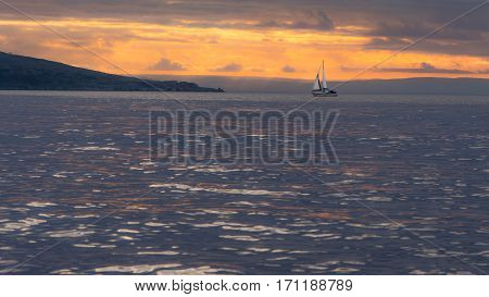 Sunset behind Brean Down in the Bristol Channel, with yacht. Spectacular sky and clouds seen from Weston-super-Mare in Somerset UK with fort on peninsula