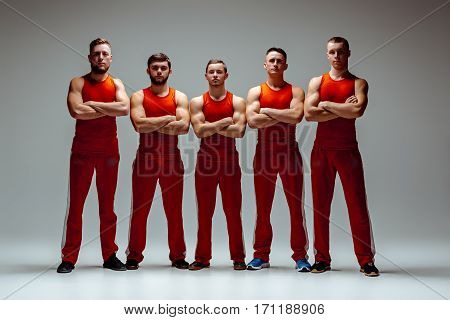 The group of gymnastic acrobatic caucasian men posing on gray studio background