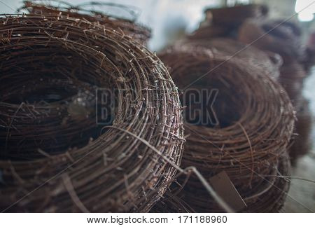 The rusty hank of an old barbed wire lying in military warehouses waiting for
