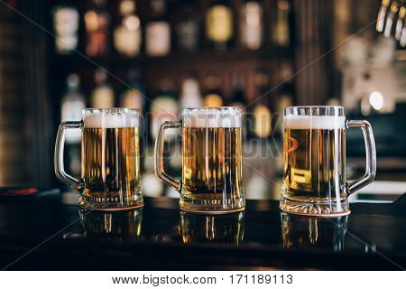 Three glasses with beers in a pub background