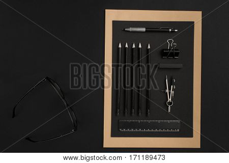 Mix of office supplies on a modern office desk. Object on a black background. Top view. Still life. Copy space