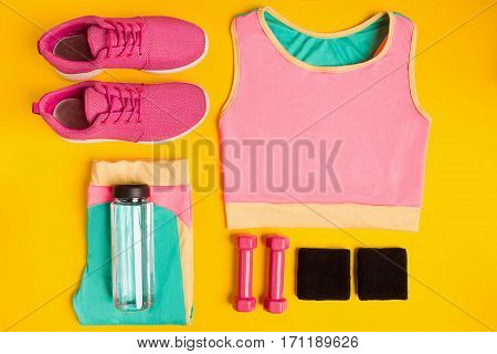 Fitness accessories on yellow background. Sneakers, bottle of water, dumbbells and sport top. Top view. Still life