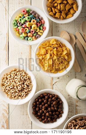 Variety of cold cereals in white bowls on white wooden table, quick breakfast for kids overhead shot