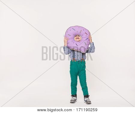 kid boy playing with toy pillow in shape of donut. Full body length isolated on white background. Funny Little kid holding a big size colorful donut