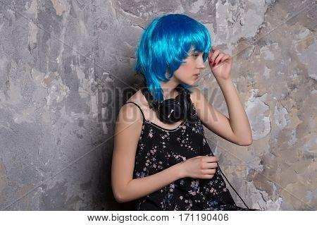 young pretty woman or sexy girl in hair wig blue color with cute face in musical headset or headphones on grey wall textured background