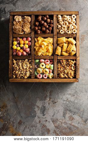 Variety of cold cereals in a wooden box, quick breakfast for kids overhead shot