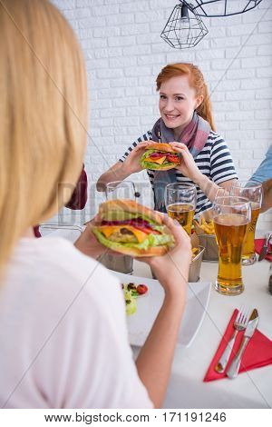 Girls are eating burgers during common meal at restaurant