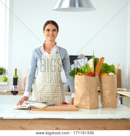 Portrait of a smiling woman cooking in her kitchen .