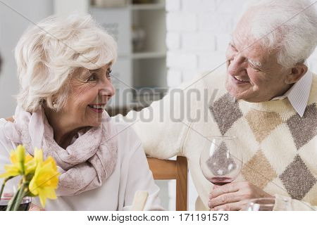 Elderly marriage looking at each other with happiness and love during family dinner