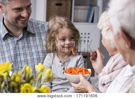 Grandmother feeding with healthy carrots grandchild sitting on her father's lap