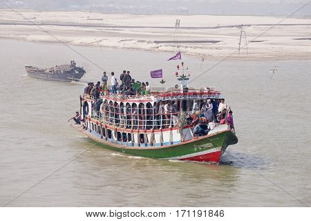 CHHOTA DHULANDI, BANGLADESH - FEBRUARY 19, 2014: Unidentified passengers cross Padma river on Daulatdia ferry boat at Chhota Dhulandi, Bangladesh. Passenger ferry boats are often overloaded in Bangladesh.