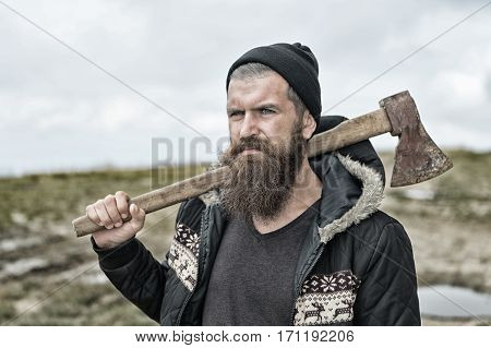 Handsome man hipster or guy with beard and moustache on serious face in hat and jacket holds rusty axe with wooden hilt outdoor on mountain top against cloudy sky on natural background copy space