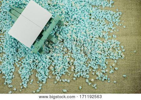 Blue Easel With White Paper For Inscriptions On The Crumbled Blue Gravel