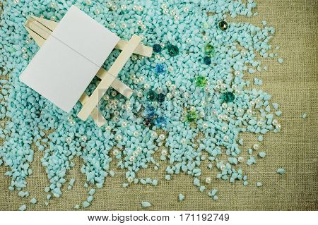 White Easel With Paper For Inscriptions On Gravel With Pearl And Blue Beads.