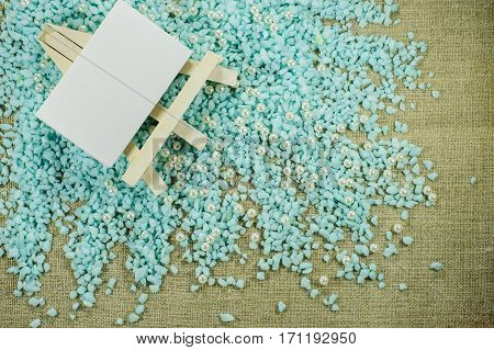 White Easel With White Paper For Inscriptions On The Crumbled Blue Gravel.