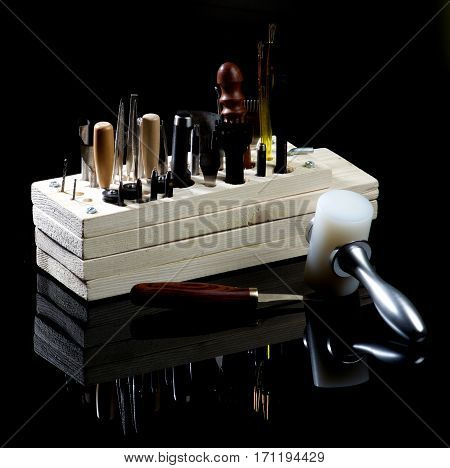 Arrangement of Various Tanneries Tools for Cutting and Piercing of Leather in Wooden Box with Reflection on Black Shiny background
