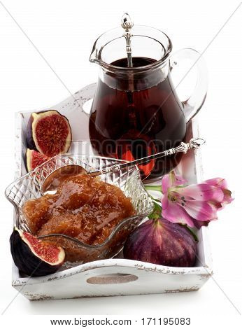 Homemade Homemade Fig Jam in Glass Kremanka with Fresh Fig Fruits Glass Cup of Tea and Flowers in White Wooden Tray closeup on White background