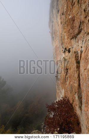 Rock climber ascending a challenging cliff. Extreme sport climbing. Freedom, risk, challenge, success.