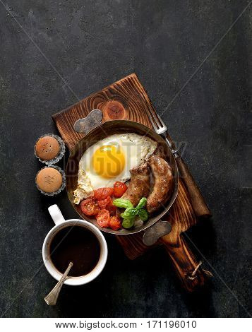 breakfast in a frying pan, fried eggs, sausages and tomatoes on a dark background
