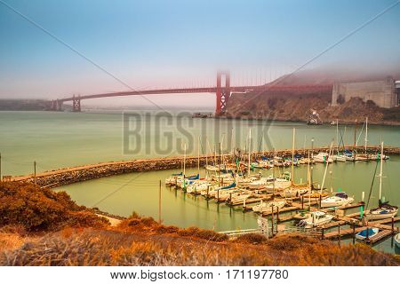 Aerial view of Golden Gate Bridge with typical fog and Presidio Yacht Club in Horseshoe Bay, Sausalito, California, United States. Symbol and landmark of San Francisco. Travel and holidays concept.