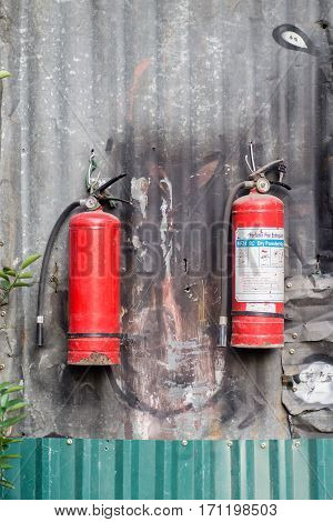 the red fire extinguisher on corrugated wall