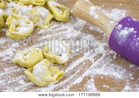 Several raw yellow ravioli with plunger on the flour