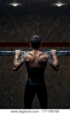 Back view male muscular athlete doing pull up exercise on horizontal bar. Fitness, gymnastics workout in gym.