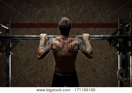 Back view of muscular man with naked torso doing pull up exercise on horizontal bar. Gymnastics, fitness workout in gym.