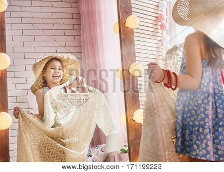 Happy girl dresses up at home. Funny lovely child is having fun in kids room.
