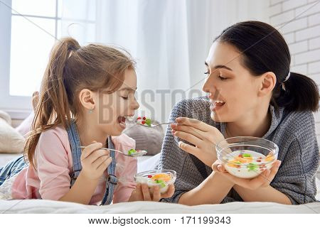 Happy loving family. Mother and her daughter child girl are eating fruity salad on the bed in the room.