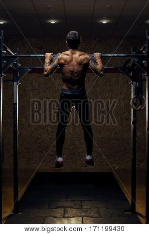 Full length shot of muscular man with naked torso doing pull up exercise on horizontal bar. Fitness workout in gym.