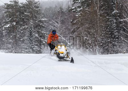 The sportsman on a snowmobile moving through deep snowdrifts in the winter forest in the mountains of the Southern Urals.