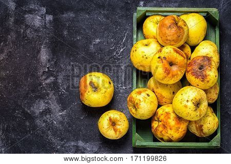 box full of of stale green apples on a dark black cement background top view copy space