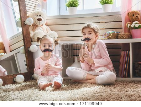 Funny family playing at home. Two cute little children girls with paper accessories. Sisters are holding paper mustache on sticks.