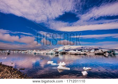 The concept of northern extreme tourism. The ice floes and cirrocumulus clouds of lagoon Jokulsarlon, Iceland