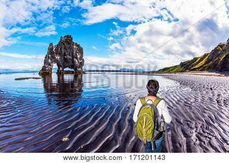 Woman with a green backpack admires Rock Hvitsercur. Northern coast of Iceland. Concept of extreme northern tourism
