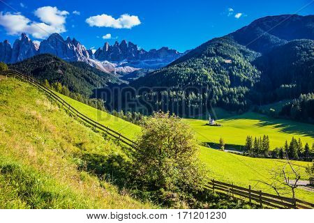 Little picturesque church of Santa Maddalena in valley Val di Funes.  Sunny autumn day in Dolomites, Tirol. Rocky peaks and forested mountains surrounded by green Alpine meadows
