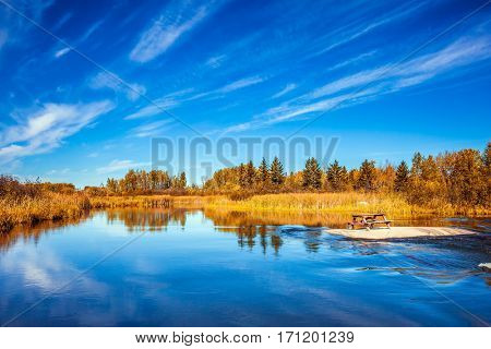 The concept of ecological and extreme tourism. Thin flying cirrus clouds over broad Winnipeg River, Old Pinawa Dam Park. On the island is a wooden bench for tourists