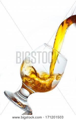 The glass is poured brandy from a decanter on a white background
