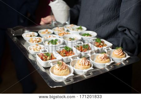 A waiter with a tray of snacks. Server holding a tray of appetizers at a banquet