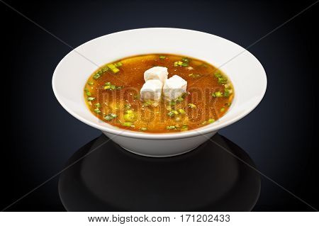 Miso soup in a white plate on a black background