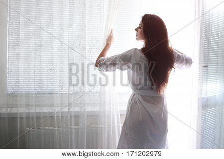 beautiful woman standing near window and opening the curtains to see the light