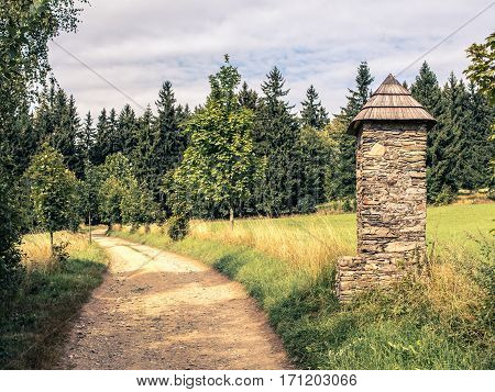 Stone chapel or shrine next to the beaten track, relaxed walk, summer countryside landscape, bottom copy space