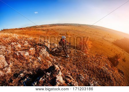 fisheye of cyclist standing with mountain bike at sunrise against bright sun and blue sky. sping season. Horisontal fisheye wide angle photo. Beautiful landscape with hill.